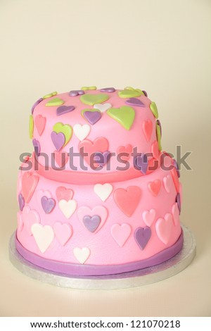 Beautifully decorated round double tier birthday cake with pink fondant plastic icing and pink, green, white and purple hearts all over, on a cream background - stock photo