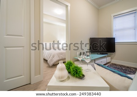 Beautifully decorated side table in a living room with a bedroom in the background. Interior design. - stock photo
