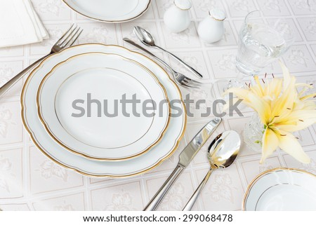 Beautifully decorated table with white plates, crystal glasses, cutlery and flowers on luxurious tablecloths - stock photo