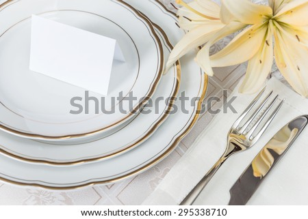 Beautifully decorated table with white plates, crystal glasses, linen napkin, cutlery and flowers on luxurious tablecloths, with guest card - stock photo