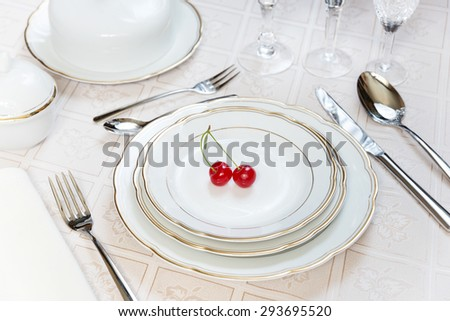 Beautifully decorated table with white plates, crystal glasses, linen napkin, cutlery and tulip flowers on luxurious tablecloths - stock photo