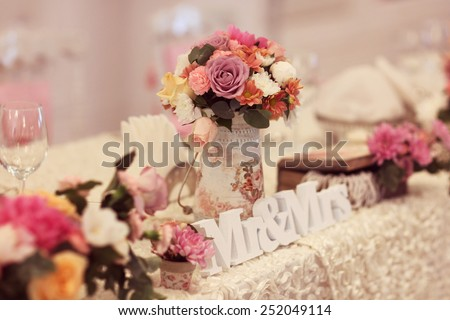 Beautifully decorated wedding table with flowers and MR&MRS letters  - stock photo
