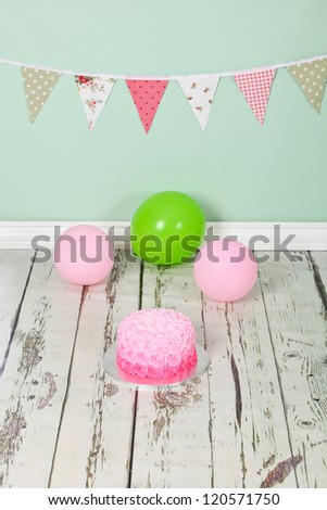 Beautifully designed pink ombre butter icing birthday party cake on distressed wooden white washed floor and green background with green and pick flag bunting and balloons - stock photo