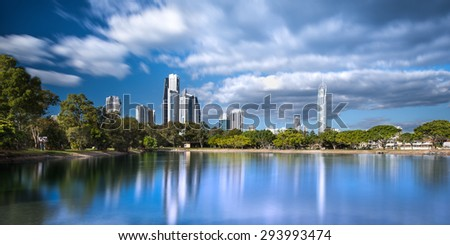 Beautifully Dramatic Daytime Long Exposure View of the Gold Coast Skyline Reflecting in the Canal with a Park on a Sunny Day, Surfers Paradise, Queensland, Australia - stock photo
