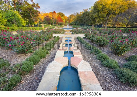 Beautifully landscaped urban rose garden on a colorful autumn day in Texas - stock photo
