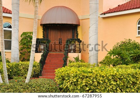 Beautifully landscaped yard with palms and lush tropical shrubbery leading to the double door entryway. - stock photo