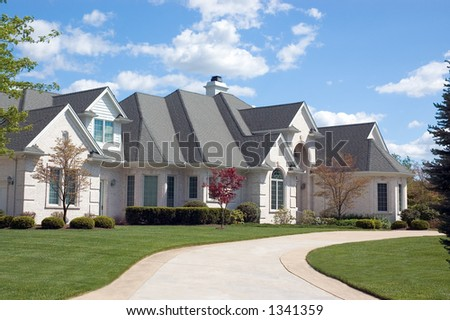 Beautifully, large and expensive  new home. This house features lots of roof peaks and a circular driveway. Just one of many new home or house photos in my gallery. - stock photo