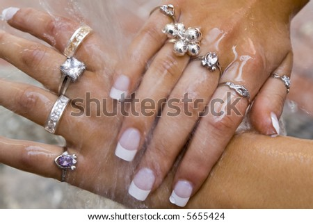 Beautifully manicured women's hands covered in rings being washed outside under free flowing water