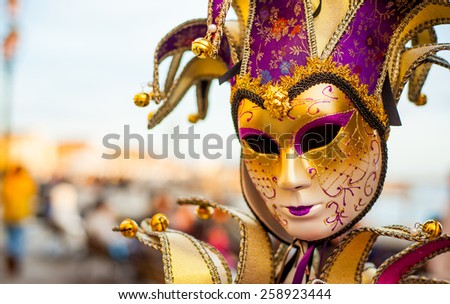 Beautifully painted ornate golden venetian mask hanging ob blurred background - stock photo