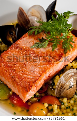 Beautifully plated salmon fillet garnished with colorful green parsley.  Served over a couscous and seafood salad featuring mussels, clams, tomatoes and brussels sprouts. - stock photo