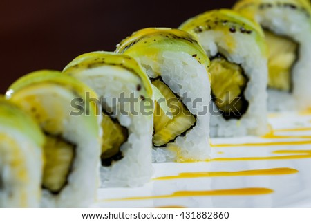 beautifully presented and freshly prepared sweet kiwi and pineapple sushi roll served on a white plate - stock photo