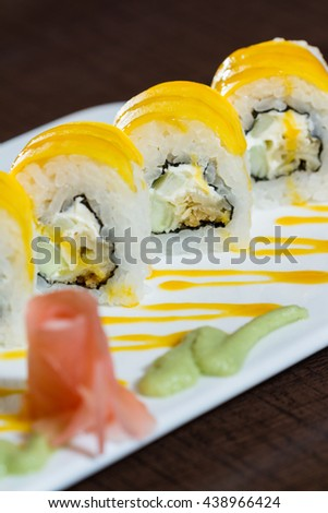 beautifully presented and freshly prepared sweet mango sushi roll served on a white plate - stock photo
