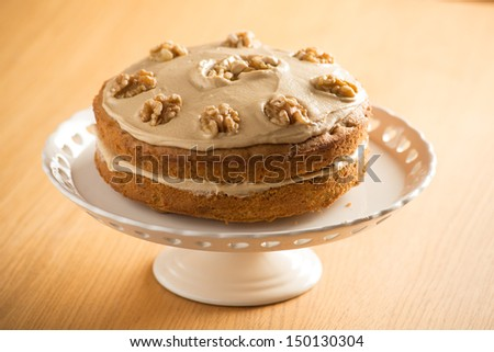 Beautifully presented Coffee and Walnut cake on a white cake stand - stock photo