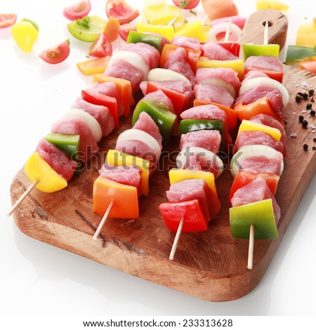Beautifully presented fresh meat and vegetable kebabs with diced colorful sweet bell pepper and onion standing ready for grilling or roasting on a wooden board over white - stock photo