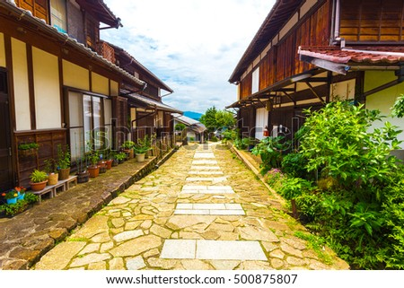 Beautifully restored traditional wooden houses line the sides of a stone path on the ancient Nakasendo trail during daytime in Magome, Kiso Valley, Japan. Horizontal