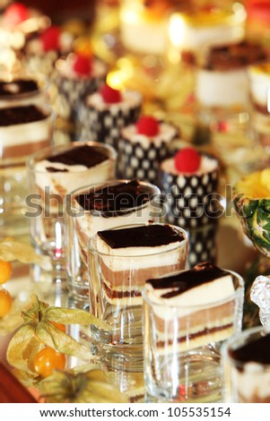 Beautifully served individual cakes and desserts on a buffet table at a luxury event - stock photo