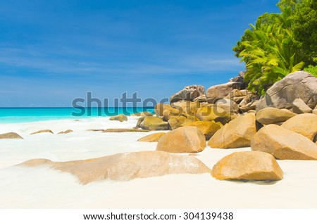 Beautifully shaped granite boulders and a perfect white sand at the famous Anse Georgette, Praslin island, Seychelles - stock photo