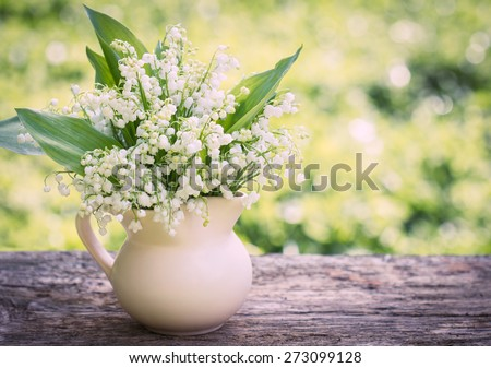 Beautifyl bouquet of lilies of the valley on the table - stock photo
