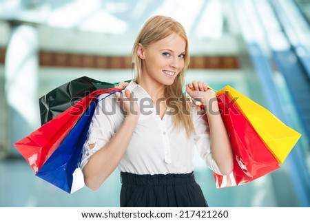 Beautilful young woman carrying shopping bags. Isolated on white - stock photo