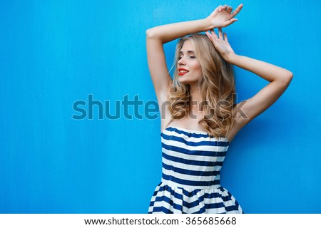 beautty fashion portrait of blonde woman with red lips and stripped dress. Fashion portrait. Smiling blonde woman in fashionable look. Sea style. On blue background. Style and hot girl outdoor. - stock photo