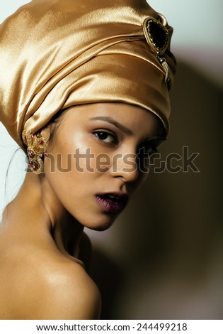 beauty african woman in shawl on head, very elegant look with gold jewelry close up - stock photo