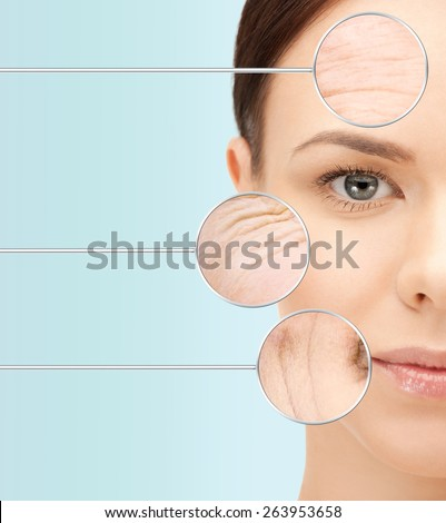 beauty, aging, people, skincare and health concept - beautiful young woman face with wrinkles over blue background - stock photo