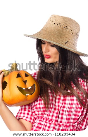 Beauty and a Pumpkin - Attractive girl in a vintage dress and a straw hat holding a Halloween pumpkin - stock photo