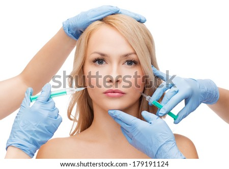 beauty and cosmetic surgery concept - woman face and beautician hands with syringes - stock photo