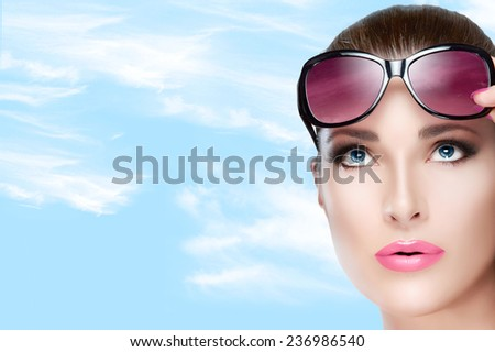 Beauty and Fashion Concept - Closeup Pretty Young Woman Wearing Stylish Red Violet Sunglasses on Forehead, Looking up. High fashion portrait over blue sky with white clouds and Copy Space to the Left - stock photo