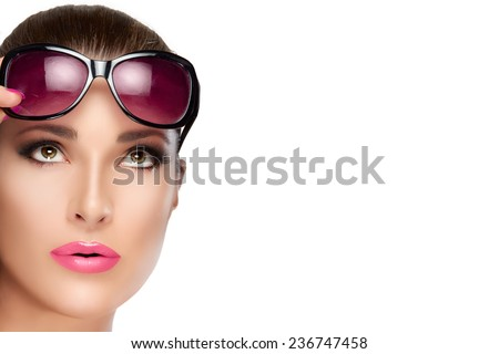 Beauty and Fashion Concept - Closeup Pretty Young Woman with Stylish Red Violet Sunglasses on Forehead, Looking up. High fashion portrait Isolated on White with Copy Space. Bright makeup and manicure.