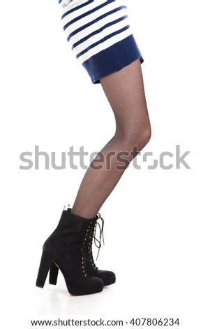 Beauty and fashion of female. Long slim attractive woman legs in tights and high heels boots. Part body girl in striped dress skirt isolated on white. - stock photo