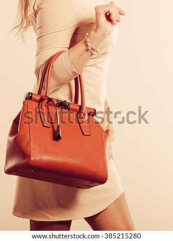 Beauty and fashion. Stylish fashionable woman wearing bright dress holding brown bag handbag, studio shot - stock photo