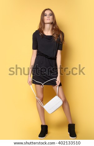 Beauty and fashion. Stylish girl with white leather bag in black dress on yellow background.