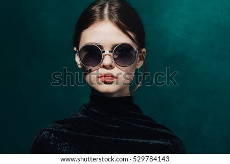 Beauty and fashion woman in black sunglasses on a bright colored background .