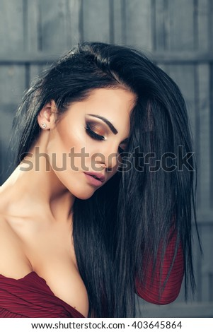 Beauty and fashion. Young woman closeup in fashionable red dress in studio