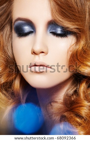 Beauty and health, cosmetics and make-up. Close-up portrait of beautiful woman model with long curly shiny hair, glitter evening make-up. Colorful light spots - stock photo