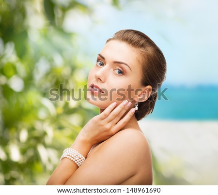 beauty and jewelery concept - beautiful woman with pearl earrings and bracelet - stock photo