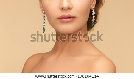beauty and jewelry concept - beautiful woman in diamond and emerald earrings - stock photo