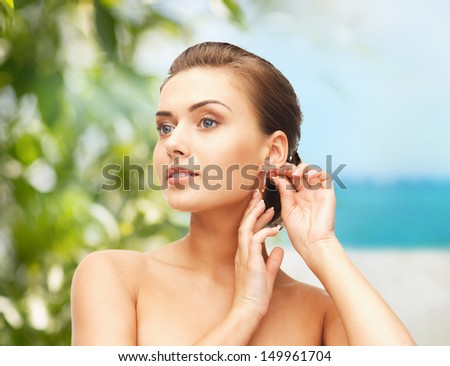 beauty and jewelry concept - beautiful woman trying on gold earrings - stock photo