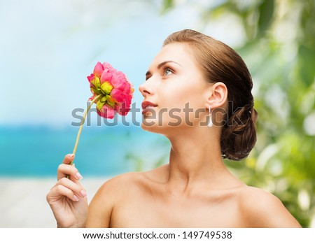 beauty and jewelry concept - woman wearing earrings and smelling flower - stock photo