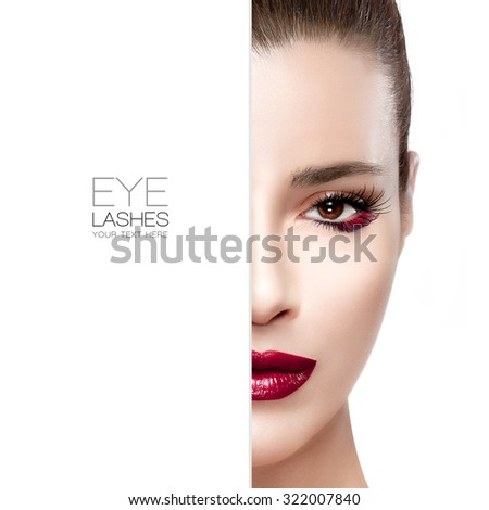 Beauty and Makeup concept with half face of a beautiful young woman with red lips and festive eyelashes. Perfect skin. Trendy red lips. High fashion portrait isolated on white with sample text - stock photo