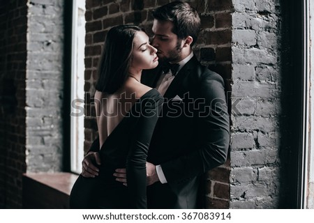 Beauty and passion. Beautiful young loving couple bonding to each other while both standing against brick wall indoors - stock photo