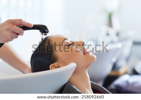 beauty and people concept - happy young woman with hairdresser washing head at hair salon - stock photo
