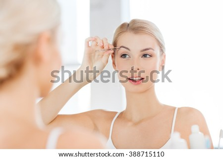 beauty and people concept - smiling young woman with tweezers tweezing eyebrow and looking to mirror at home bathroom - stock photo