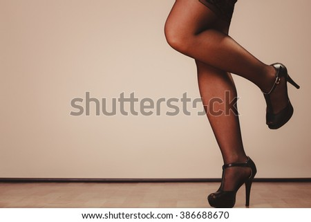Beauty and sexuality of women. Sexy part body woman model wearing black stockings. Female legs in high heels. - stock photo