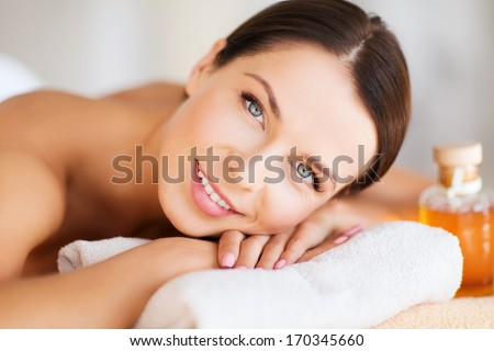 beauty and spa concept - happy woman in spa salon lying on the massage desk - stock photo
