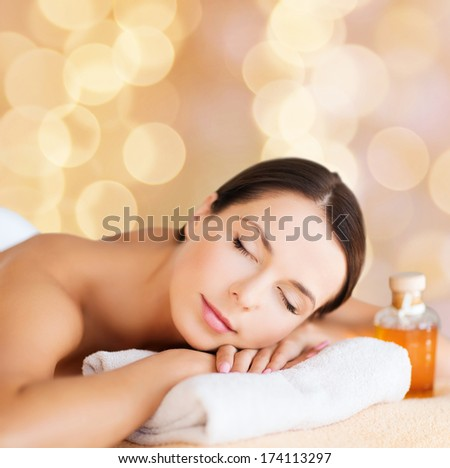 beauty and spa concept - happy woman in spa salon lying on the massage desk
