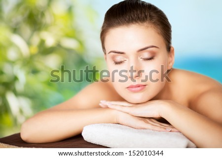 beauty and spa concept - woman in spa salon lying on the massage desk - stock photo