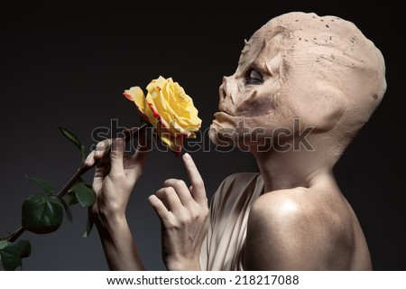 Beauty and the beast. Ugly witch with beautiful flower in hand. - stock photo