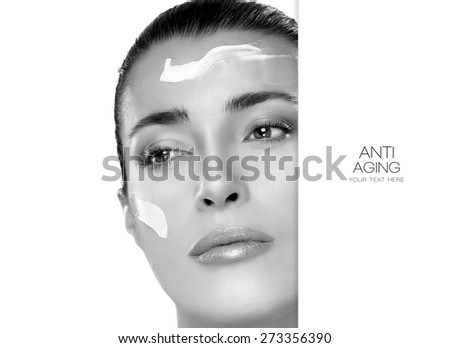 Beauty. Anti Aging and skin care concept. Monochrome portrait of a gorgeous woman with cosmetic cream on her cheek and forehead, blank copy space alongside with sample text. Spa treatment - stock photo